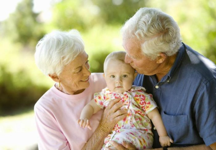 Счастливые бабушка и дедушка держат младенца