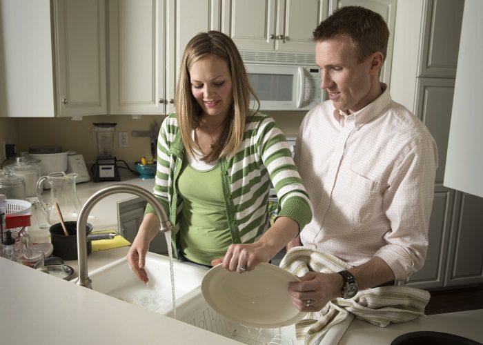 Жена и муж вместе моют посуду