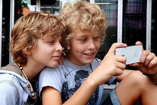 Мальчик держит в руках айфон и смотрит в него, другой мальчик прильнул к нему и тоже смотрит