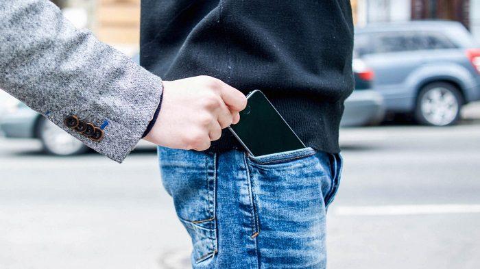 У человека вытаскивают из кармана айфон
