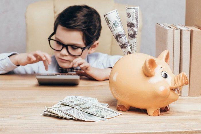 Мальчик считает на калькуляторе, перед ним стоит свинья-копилка, из которой торчат доллары, они же рядом лежат на столе