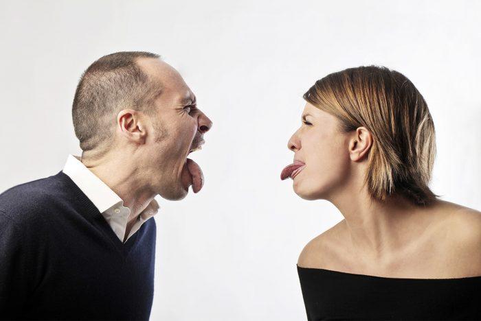 Мужчина и женщина показывают язык друг другу