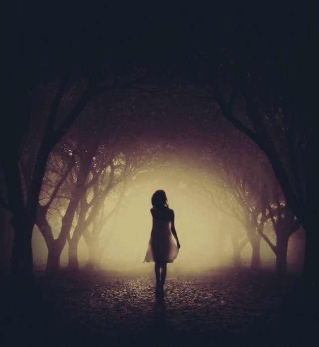 Женщина идёт одна по тёмной алее