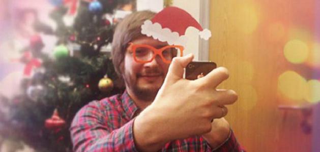 Мужчина делает новогоднее селфи в очках и колпаке