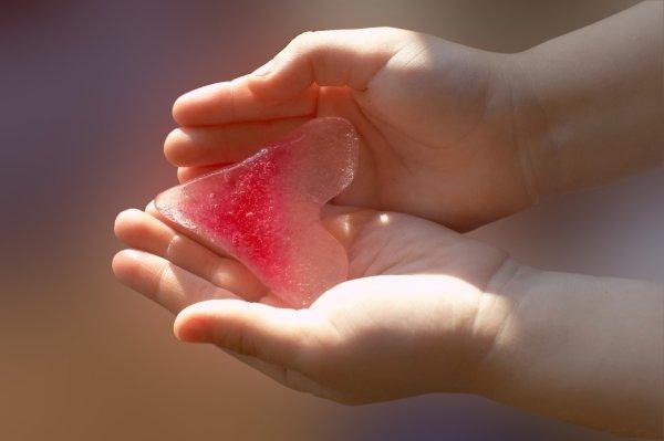 Льдинка на ладошках в форме розового сердечка