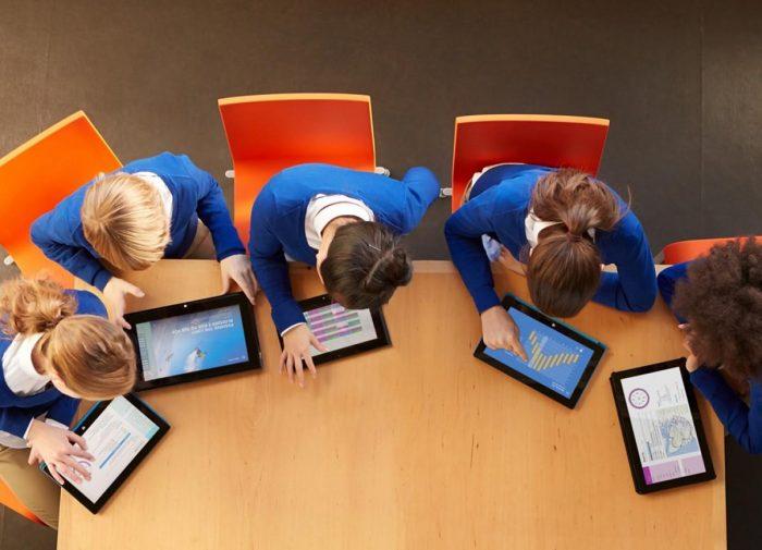 Пятеро детей склонились над планшетами