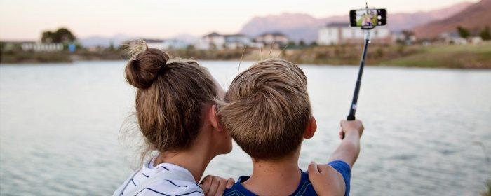 Девочка и мальчик делают селфи у реки