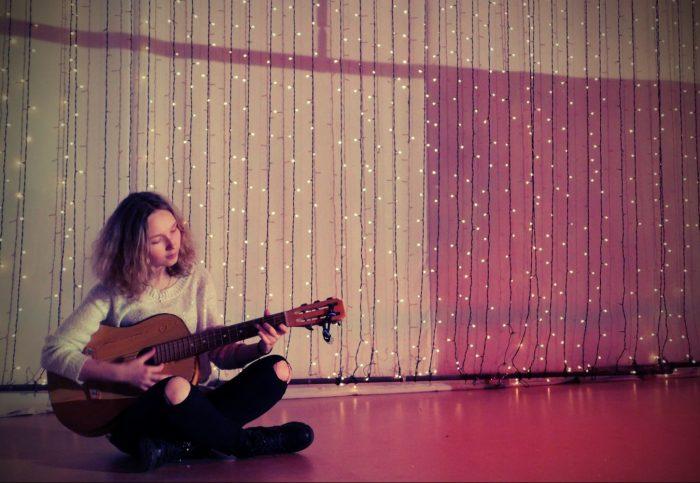 Девочка в комнате играет на гитаре