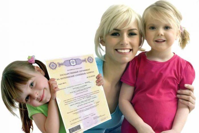 Мать с двумя дочками держит в руках сертификат на материнский капитал