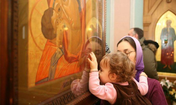 Девочка без головного убора целует икону, дочку держит на руках мама (в платке)