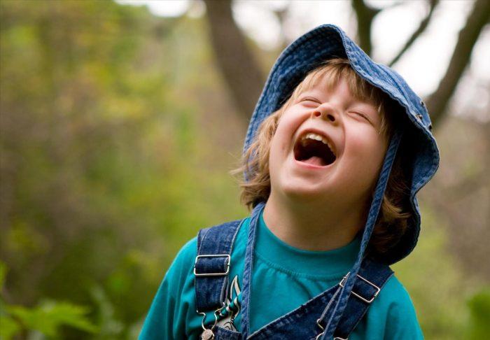 Мальчик хохочет, широко открыв рот