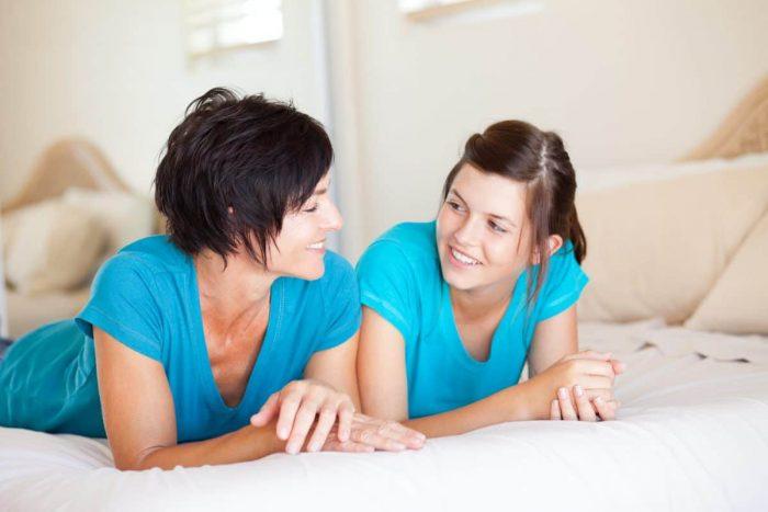 Мать и дочь-подросток лежат рядом на кровати и беседуют