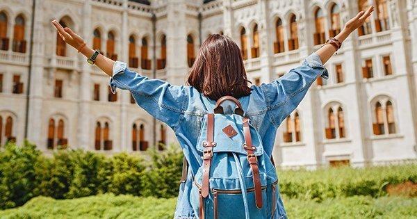 Девушка с большим рюкзаком у стен учебного заведения