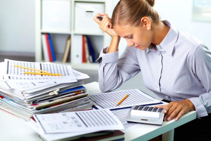 Бухгалтер за работой (смотрит в отчёт, рядом ещё стопка бумаг)