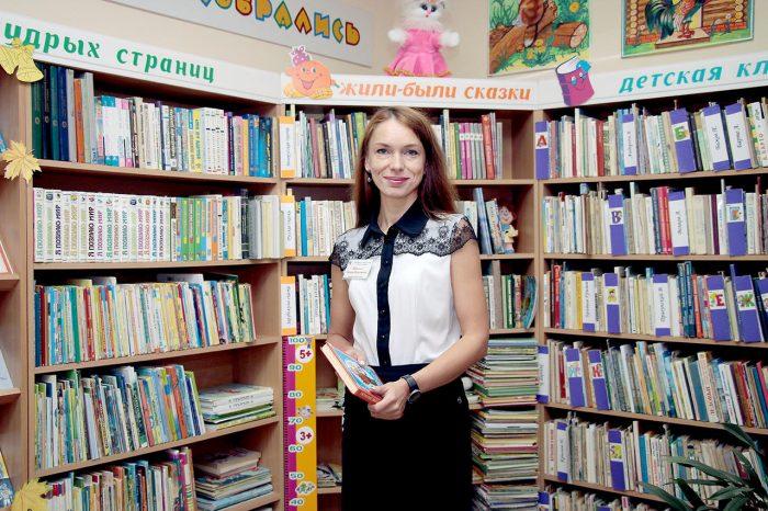 Библиотекарь рядом с книжными полками