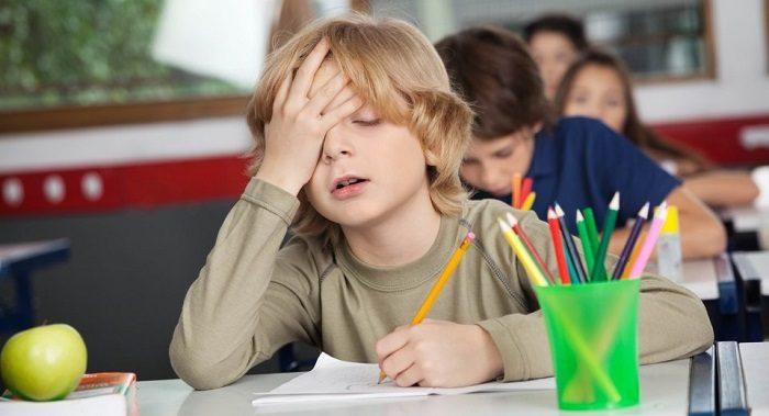 Мальчик на уроке хватается за голову с усталым видом