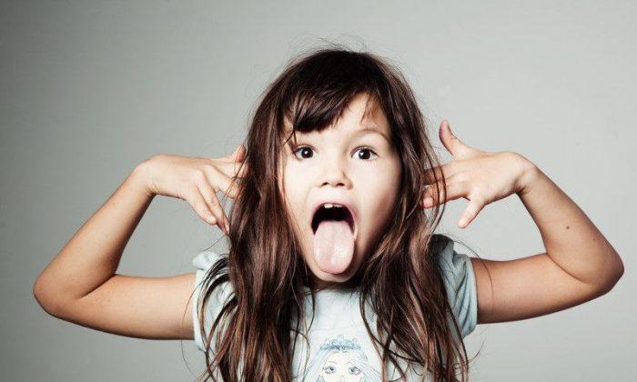 Девочка кривляется, высовывает язык