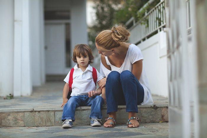 Мальчик сидит на улице на плитке, мама что-то ему объясняет