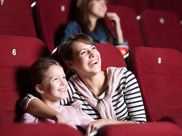 Мать с сыном смотрят фильм в кинотеатре