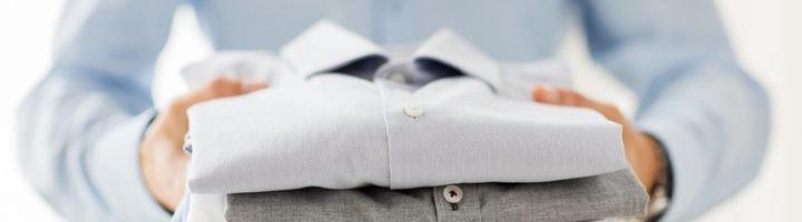 Мужчина держит стопку сложенных рубашек