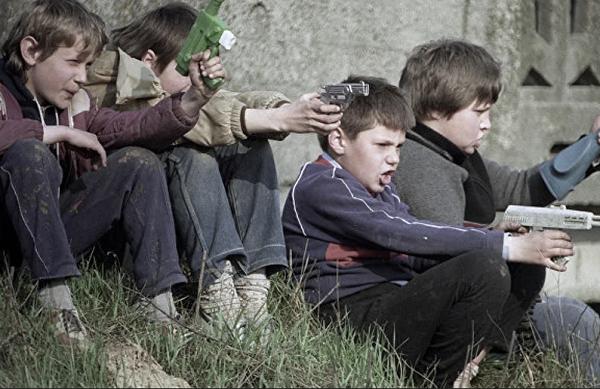 Мальчики советских времён играют в «войнушку» - стреляют из игрушечных автоматов и пистолетов