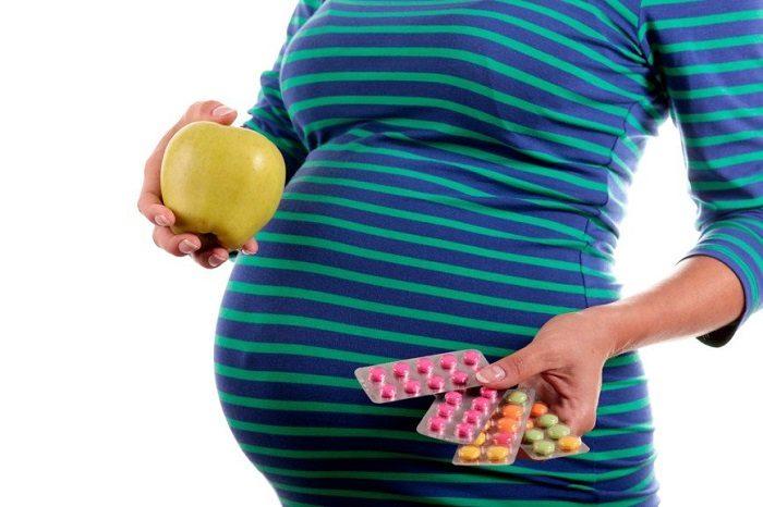 Беременная держит в одной руке яблоко, а в другой витамины