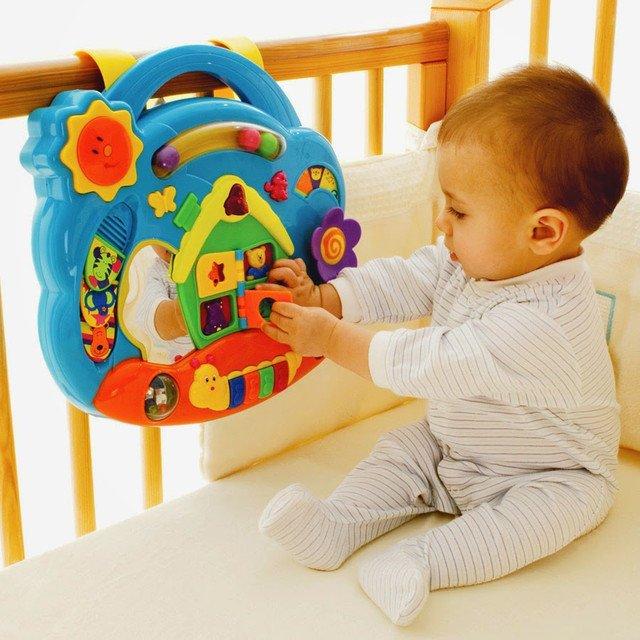 Шестимесячный малыш с развивающей игрушкой в кроватке
