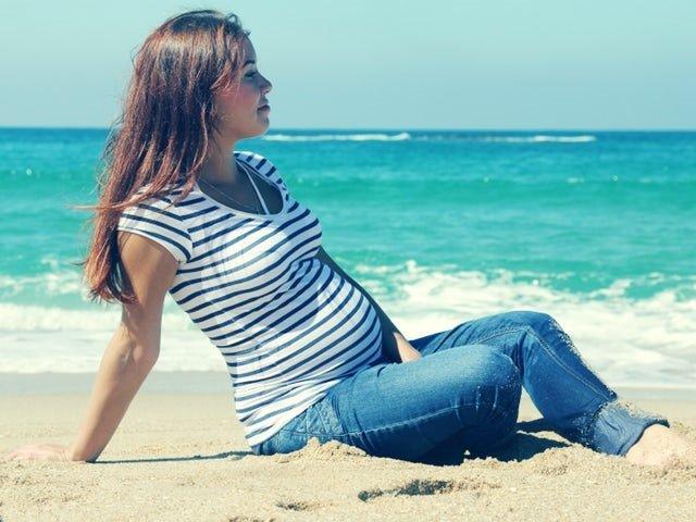 Беременная сидит на берегу моря