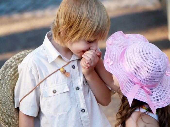 Мальчик целует руку девочки
