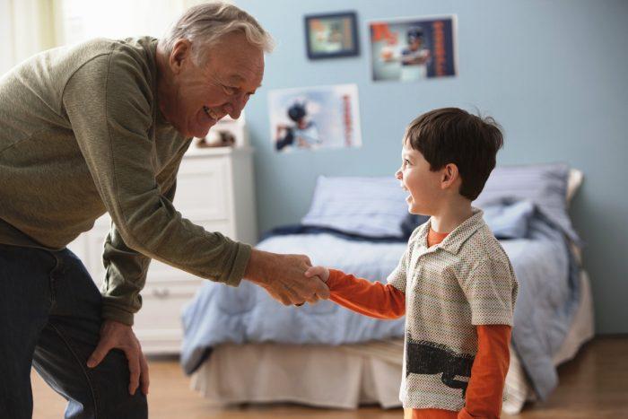 Мальчик за руку здоровается с пожилым мужчиной