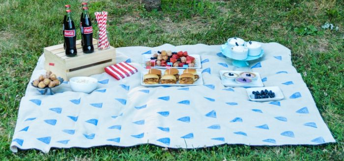 Продукты для пикника разложены на байковом одеяле