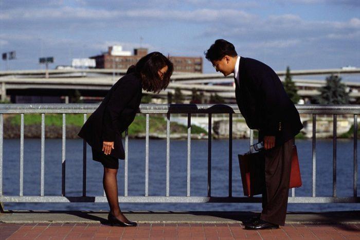 Японцы (мужчина и женщина) кланяются друг другу при встрече
