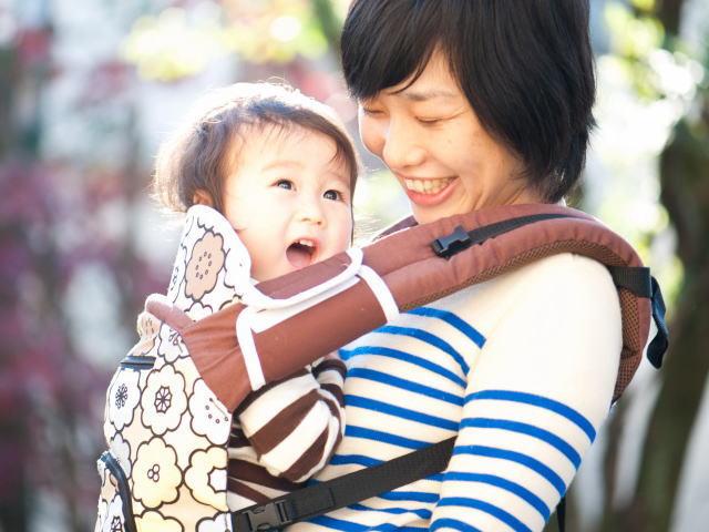 Японская мама несёт на себе маленького ребёнка