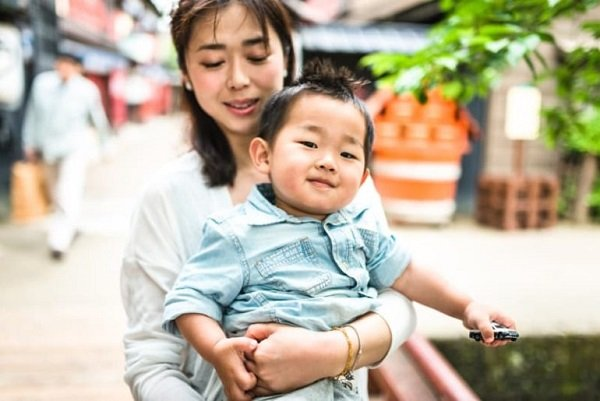 Мама-японка обнимает своего маленького сына