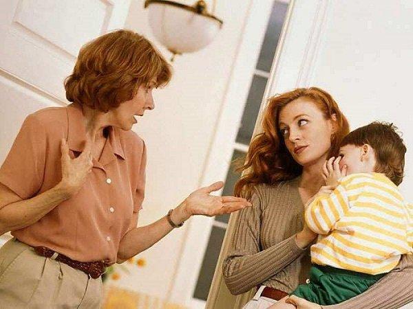 Ребёнок на руках мамы, рядом стоит бабушка и взмахивает