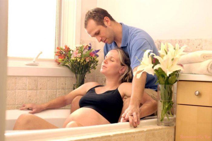 Мужчина поддерживает беременную женщину в ванной