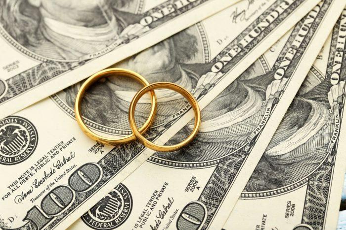 Обручальные кольца лежат на деньгах