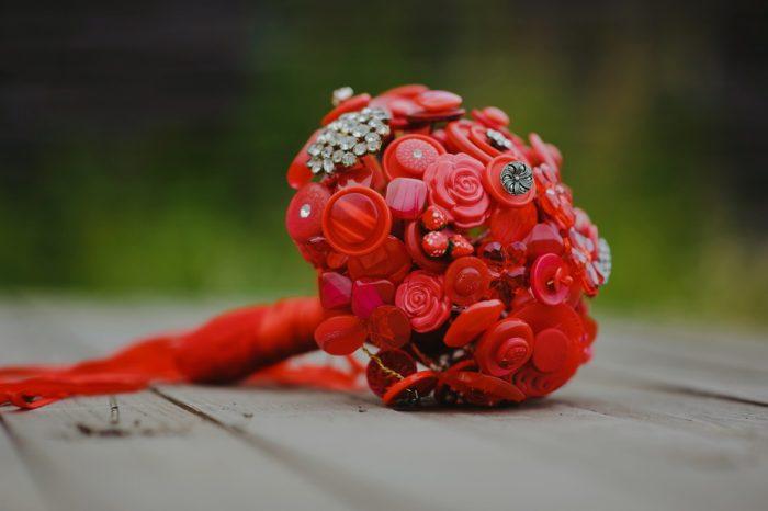свадебный букет из красных пластиковых пуговиц и фигурок