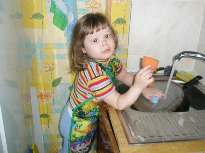 Девочка моет посуду