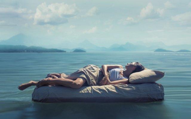 Женщина спит на постели в море