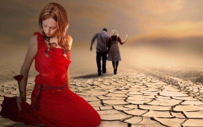 Женщина сидит на потрескавшейся земле, вдали мужчина уходит с другой