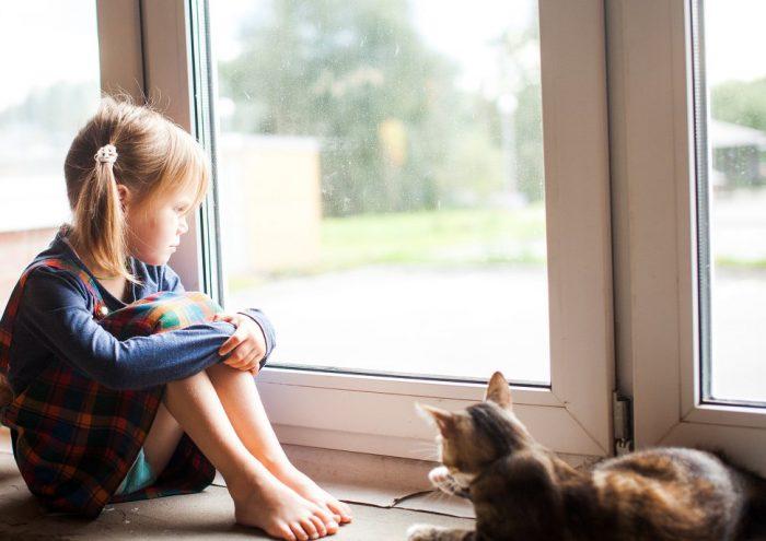 Девочка сидит на подоконнике и задумчиво смотрит в окно