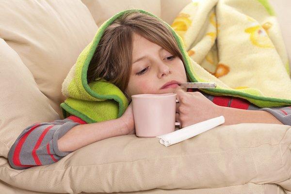 Ребёнок лежит в постели с термометром во рту и кружкой в руках