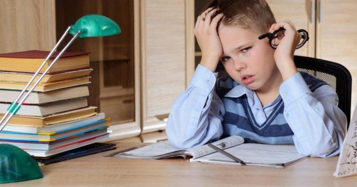 Мальчик с усталым видом сидит за столом и делает уроки