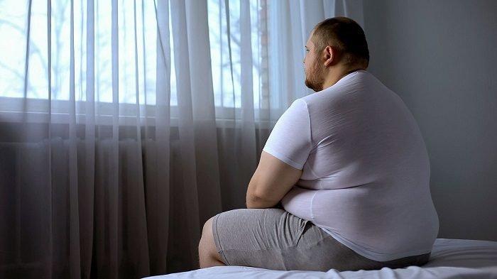 Полный мужчина сидит на кровати