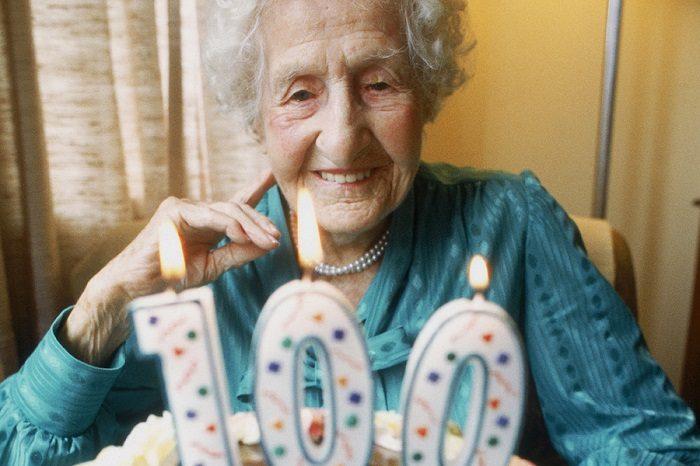 Пожилая женщина с тортом, на котором надпись «100»