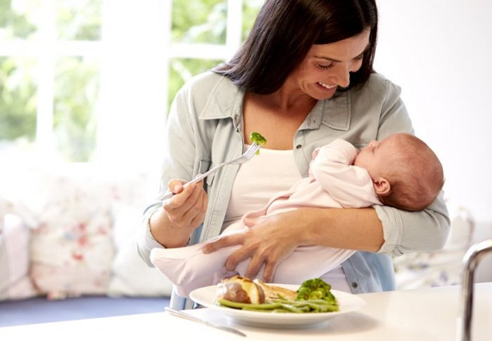 Женщина держит грудного ребёнка на руках и ест овощи