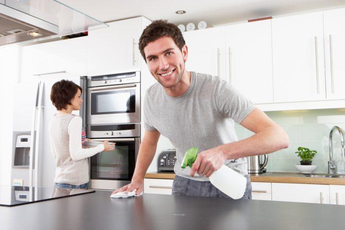 Мужчина убирает на кухне