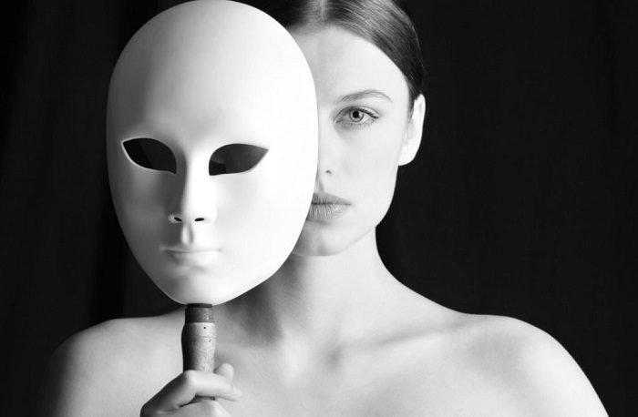 Женщина прикрывает лицо маской