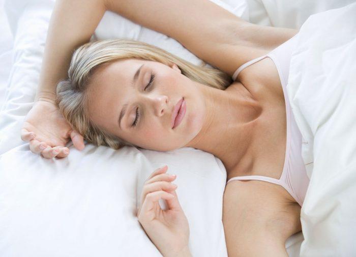 Девушка спит на спине с поднятыми вверх руками